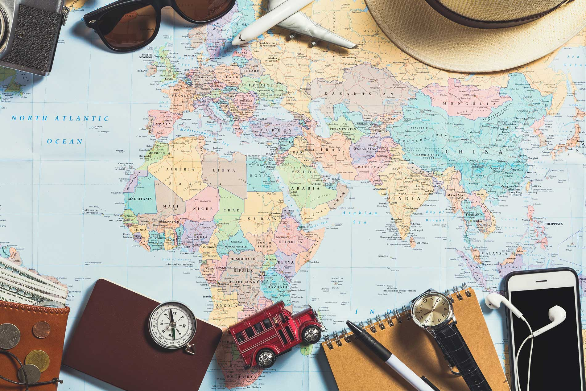 Photo of a world map with various travel elements like a passport, mobile phone, sunglasses and compass laying atop it.